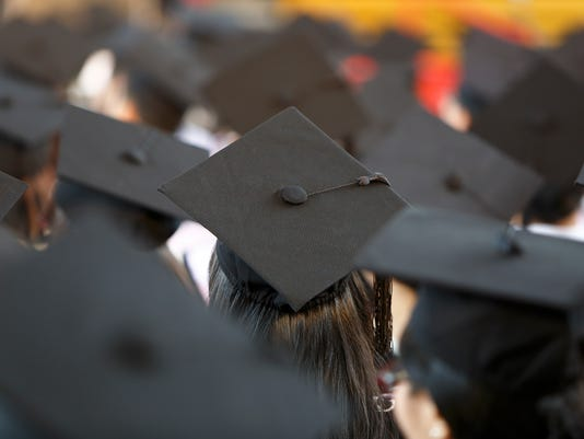 Behind view of graduates at ceremony wearing mortar hats