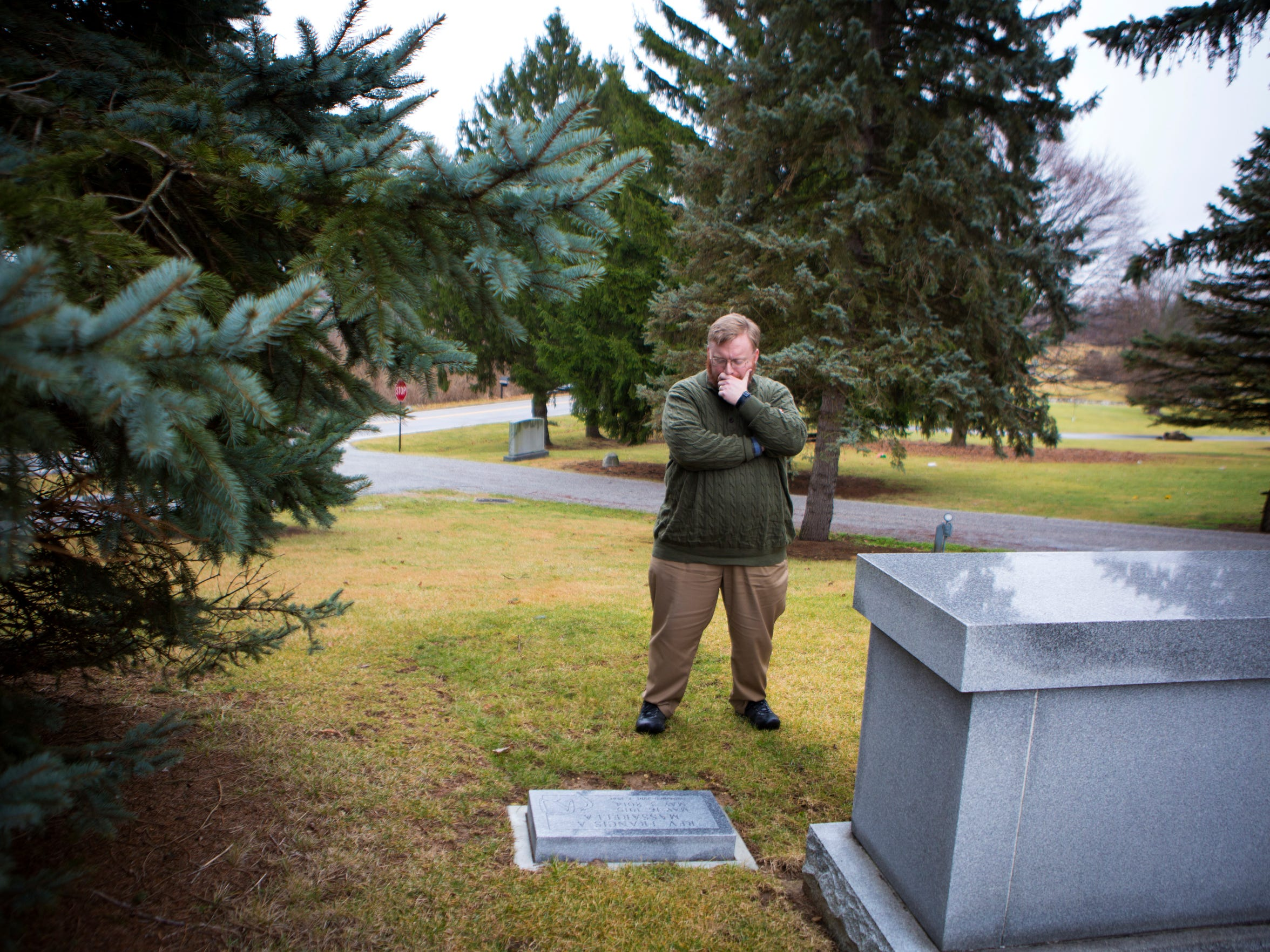 Michael stands at the grave of the Rev. Frank Massarella.
