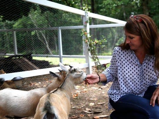 Sopchoppy Mayor Lara Edwards feeds her miniature goats,