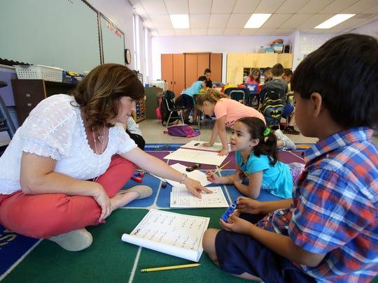 Kindergarten teacher Dana DiRubbo works with Sibyl Estrella, 5, on math problems during class at Thiells Elementary School June 15, 2017 in Thiells.