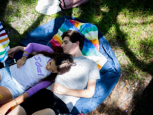 Dylan Barlow and Amanda Hoffman rest in the shade during the first-ever Naples Pride at Cambier Park Saturday, June 17, 2017 in Naples.