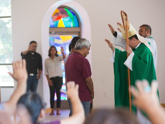 Jorge Taborda, and his sons are blessed by Bishop Oscar