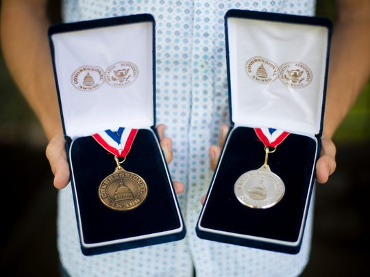 Jesse Katzeff, 18, displays the Congressional Award Bronze and Silver medals he has already received, in his Naples home Friday, June 16, 2017. Katzeff, along with his family, will travel to Washington, D.C., to receive a Congressional Award Gold Medal from U.S. Rep. Francis Rooney for his work with Teen Court, the Collier County Sheriff's D.E.P.U.T.Y. Club program and his participation in the Civil Air Patrol. He is one of 20 military youths who will receive the award.