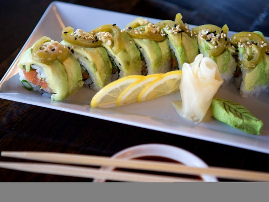 The Green Goblin roll at Jaws in Fort Collins includes salmon, asparagus, cucumber, green onion, and cilantro rolled in sushi rice and seaweed and topped with avocado and pickled jalapenos.