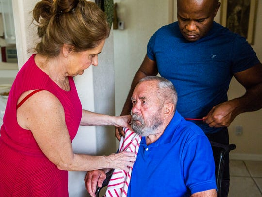 With the help of caregiver Joseph Tanis, right, Linda Ragsdale, 75, puts a bib on husband George Otto, 86, before feeding him dinner in his Naples home on Tuesday, June 20, 2017. The couple got married in 2008 and Otto was diagnosed with Alzheimer's disease in 2010. Ragsdale lives next door to her husband and gets assistance from caregivers.