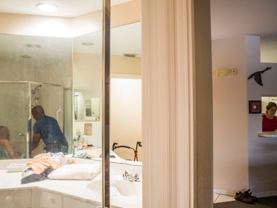 "Caregiver Joseph Tanis bathes George Otto, 86, in the shower in his Naples home while Otto's wife, Linda Ragsdale, 75, prepares his breakfast on Wednesday, June 21, 2017. Otto was diagnosed with Alzheimer's disease in 2010. Tanis has been working with Otto for four years. ""All you can do is your best and get help, and the help has kept me sane and the help has kept me alive,"" Ragsdale says of the caregivers that take care of her husband."