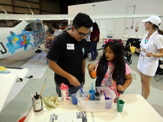 Families paint a Cessna during a SafeLaunch event against