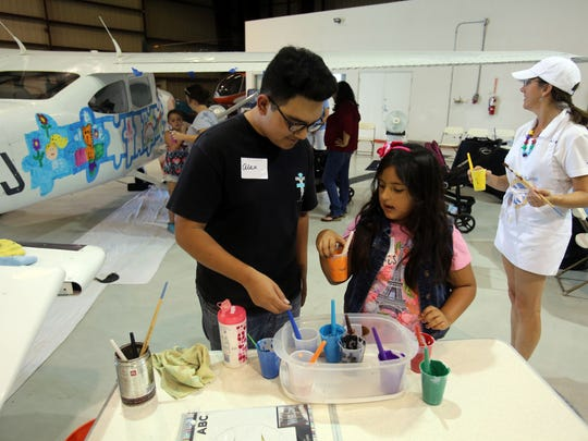 Families paint a Cessna during a SafeLaunch event against drug addiction at Signature Flight Support at Palm Springs International Airport Saturday morning, June 24, 2017. SafeLaunch brings awareness to addiction through art.