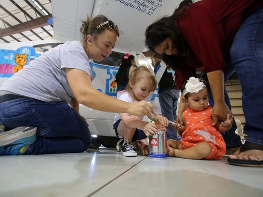 Aleana Vrabel, of Indio, left, held her daughter Elena Vrabel, 2, and Maria Estrada, of Colton, helps her daughter Daisy Estrada 1, draw on a Cessna with markers during a SafeLaunch event against drug addiction at Signature Flight Support at Palm Springs International Airport Saturday morning, June 24, 2017. SafeLaunch brings awareness to addiction through art.