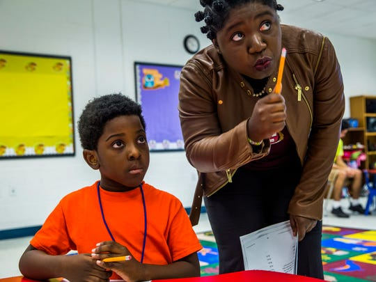 Diana Saintil works with rising second grader Latrell Joseph-Moreno while teaching a math course at the Boys and Girls Club of Collier County on Tuesday, June 27, 2017. Saintil will be attending Harvard in the fall for her masters in education policy and management.