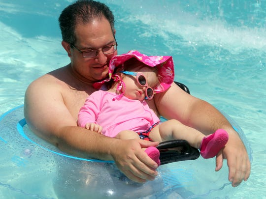 Rob Labarbera of Yonkers holds tight to his 15-month old daughter Emma, as they spend a hot afternoon in the pool at Tibbetts Brook Park in Yonkers July 21, 2016.