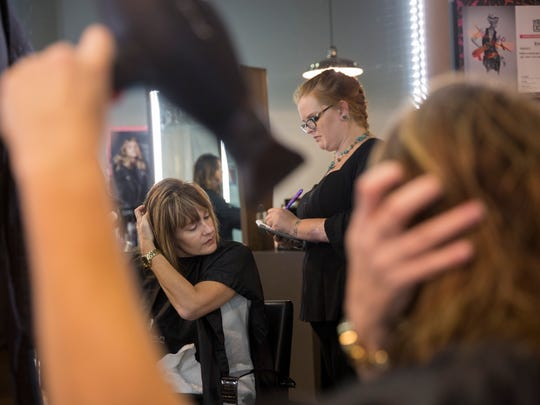 """Julie Garber blow dries her hair with the assistance of stylist, Emily Hart, during Salon Adrian's """"Blow Dry Bootcamp"""" on June 30, 2017. The event was created to teach people how to blow dry, style or curl their hair like a professional stylist."""