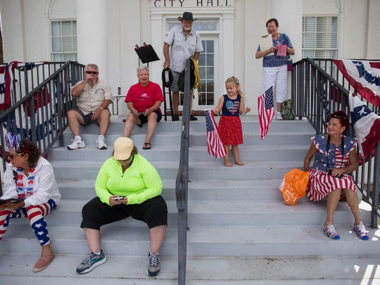 People wait on the steps of City Hall before the Independence Day parade on Saturday, July 1, 2017 in Everglades City. The parade was followed by food, face painting, arts and crafts vendors, raffles, kiddiesÕ best dressed contest, and playground games.