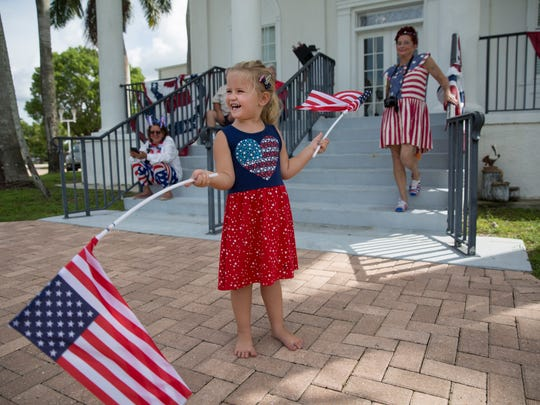 File: Abbie Spadoni-Warner, 4, waves flags around in front of City Hall before the Independence Day parade on Saturday, July 1, 2017 in Everglades City.