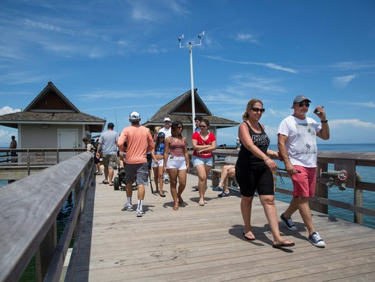 People walk down the Naples Pier on Monday, July 3,