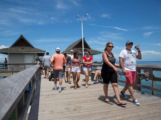People walk down the Naples Pier on Monday, July 3, 2017. The Fourth of July fireworks display will be at 9 p.m. Tuesday from a barge approximately 1,000 feet north of the Naples Pier.