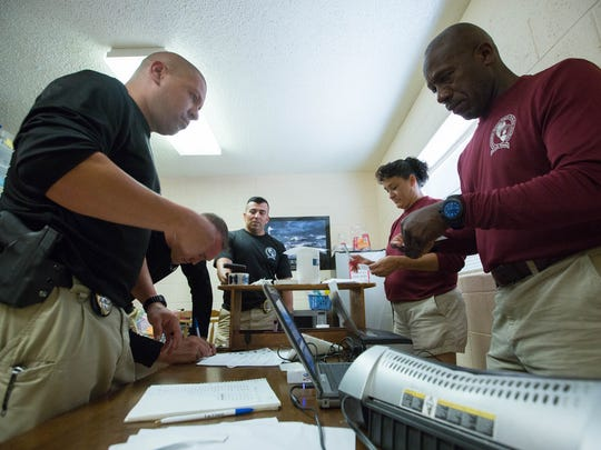Las Cruces police officers and school resource officers work on identification cards for children that visited an Ident-A-Child program, Monday, July 3, 2017 at the Children's Garden.