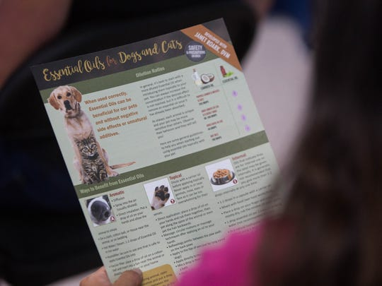Morgan Hiles, doTERRA wellness advocate, handed out an informational brochure about essential oils for dogs and cats to the class at Your Pet Space, Thursday June 29, 2017.