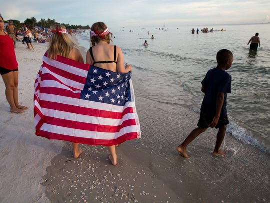 Ariah Brown, left, and Kaitlyn Porche walk down the beach holding an American flag before the fireworks show on the beach to celebrate Independence Day at the Naples Pier on July 4, 2017.