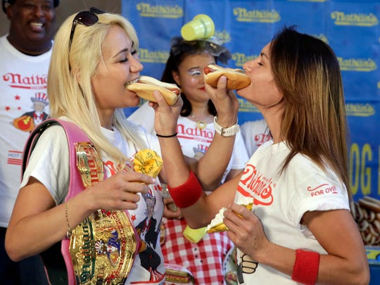 Current women's champion Miki Sudo, left, and challenger Michelle Lesco, feed each other hot dogs during weigh-on July 3 in Brooklyn.