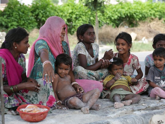 An Indian woman sits with children in Amritsar on July
