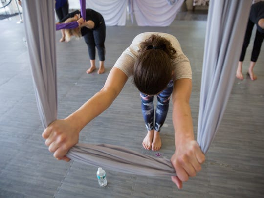 Lisa Conley, a reporter for the Marco Eagle, participates in an aerial yoga class instructed by Lorraine Gabay, at House of Flyte Aerial Studio on July 11, 2017.