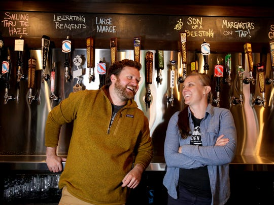 Rare Bird Brewpub co-owners (L to R) Nate Crane and Tina Schuett in front of various beer taps inside their brewery and restaurant in Traverse City, Michigan on May 26, 2017.The brewery is one of several that have been very popular in the city that has lately becoming known for a place to try various micro brews.