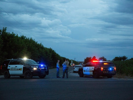 Doña Ana County Sheriff's deputies stand guard on Highway