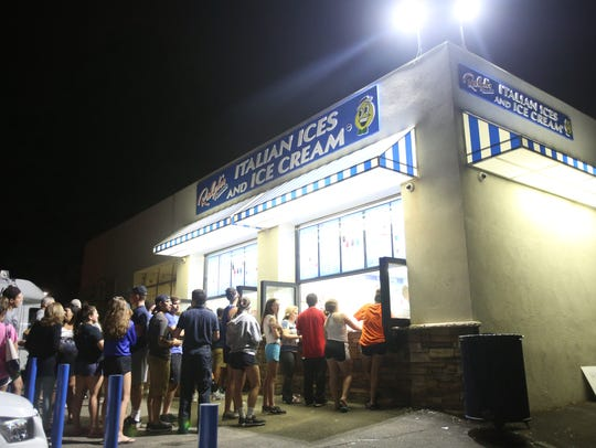 Local residents line up to get ices and ice cream at