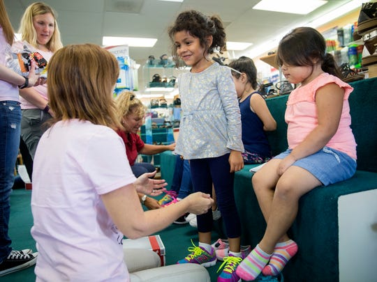 Barisa Estrada, center, a child from the Guadalupe Center in Immokalee, smiles as she is fitted for a free new pair of shoes at Snyderman's Shoes of Naples on Monday, July 17, 2017. The store has been sponsoring this event for over 20 years and is expecting around 250 kids throughout the week to get their new shoes.