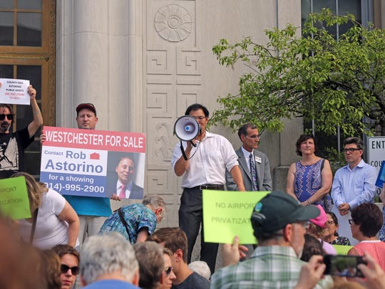 Jonathan Wang, center, of Purchase speaks during a