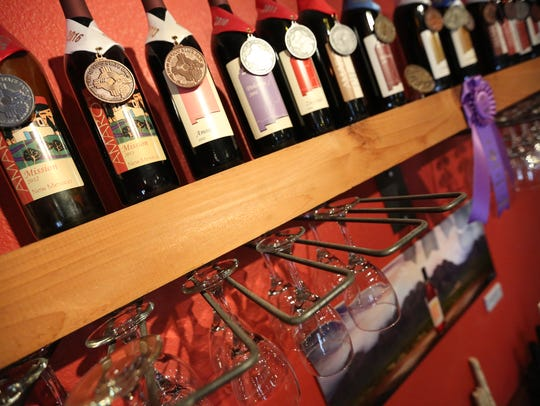 The walls are filled with wine bottles and awards at
