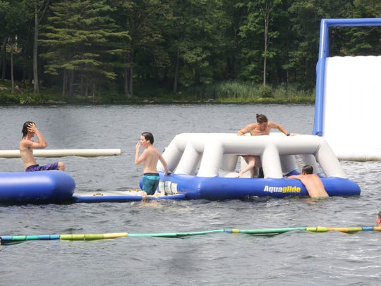 Campers swim in the water park in the lake during Day