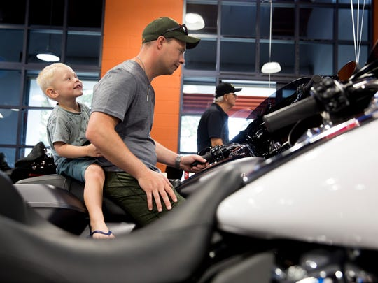 """Helge Hansen, a tourist from Oslo, Norway, tries out a new Harley Davidson with his son Sander Hansen, 3, during """"Endless Summer Bike Night"""" at Naples Harley Davidson Saturday, July 22, 2017."""