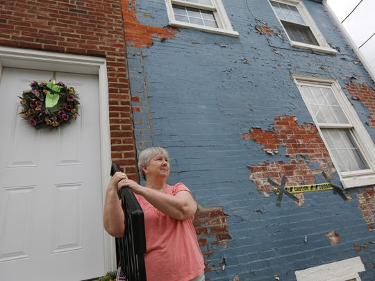 Lesley Hoehn stands outside her home that is attached to an abandoned row home on the corner of Lamotte and E. 22nd St.