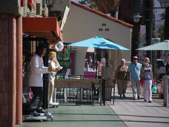 Shoppers and visitors stroll downtown on Palm Canyon