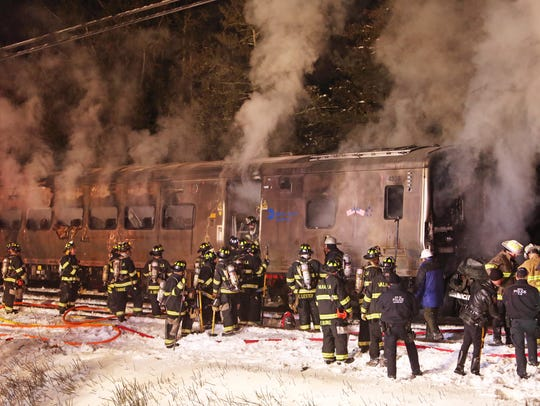 Firefighters work at the scene of a Metro-North train