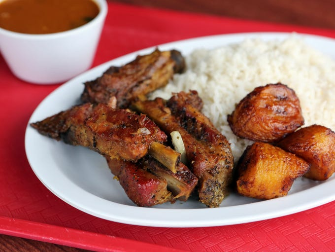 Roasted pork ribs with plantains, rice and beans at