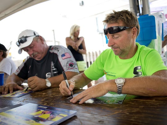 Cleveland Construction's powerboat drivers Keith Holmes, right, and Ed Smith sign autographs during a meet and greet Friday, August 7, 2015 at Vantage Point in Port Huron.