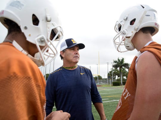Bill Kramer, head coach for the Naples High School varsity football team, talks with players at a recent practice at  Staver Field.