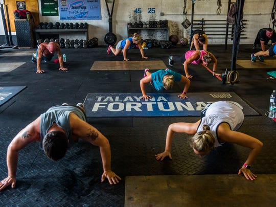 People participate in an Insanity Live workout class, taught by instructor Lauren Smith, at Crossfit Redline in East Naples on Wednesday, Aug. 3, 2017.