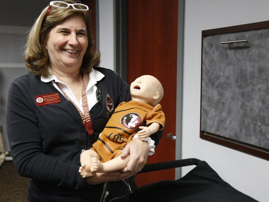 "Director of the Clinical Learning Center Debra Danforth holds ""Baby T.K.,"" an infant patient simulator, July 19."