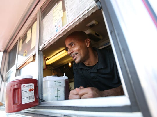 Alphonso Russell, owner of Russell's Quality Foods, smiles from his barbecue trailer off Centerville Road, near Prices Corner where he has been serving up fresh barbecue for 11 years.