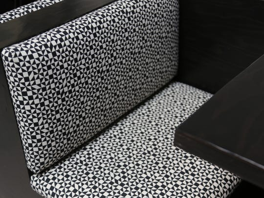 The colorful upholstery at Corktown's Katoi restaurant has been replaced with a black-and-white geometric motif for the relaunch of the restaurant after it underwent extensive fire damage.