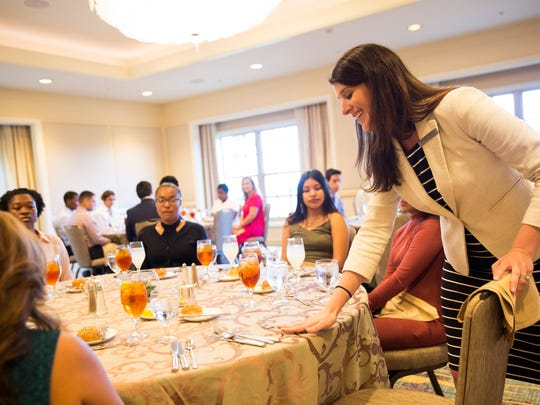Sandra Charest, the assistant human resources director at the Ritz-Carlton, Naples demonstrates when to properly use each utensil to 24 area students at lunch at the Ritz-Carlton on Thursday, Aug. 3, 2017. During the luncheon they learned proper table manners, appropriate attire and professional body language when conducting an interview.
