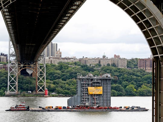A large generator passes under the George Washington Bridge as seen from Fort Lee, N.J., Tuesday, Aug. 8, 2017. A 130-foot-(40-meter)-tall steam generator built along the Hudson River outside Albany is on a barge heading south for a New Jersey power plant.
