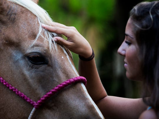Rachel Caprio, 18, pets her horse Frenchmans Honor