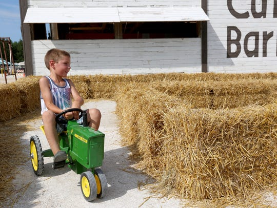 A young fair-goer rides a mini John Deere tractor during