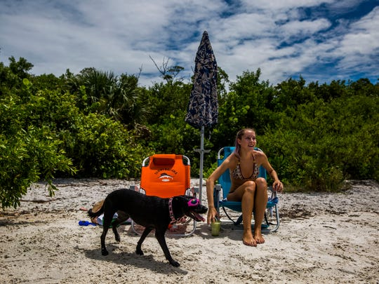Lesli Irons of Naples plays with her dog Lucy at the Bonita Springs Dog Beach on Friday, Aug. 11, 2017. Lucy has special polarized doggie sunglasses.