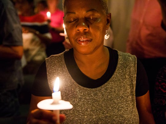 Sandra Keller, of Naples, closes her eyes in a moment of silence during a candlelight vigil during Showing Up Against Hate: An Anti-Racism Vigil event at the Unitarian Universalist Congregation in Naples on Monday, Aug. 14, 2017.